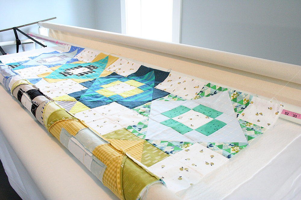 loading a quilt top roll until the top edge reaches the registration line