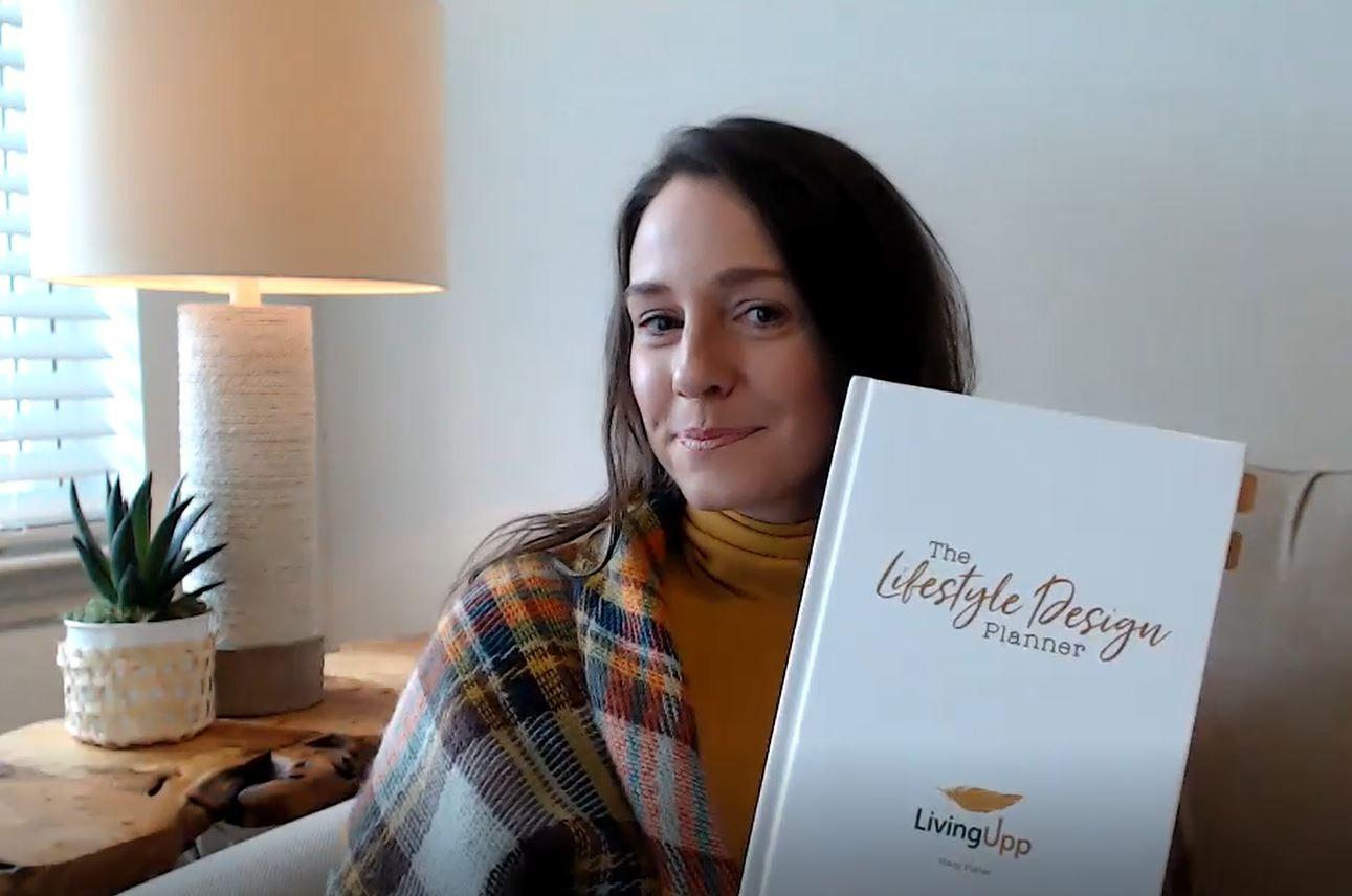 Author and LivingUpp founder Stacy Fisher holding The Lifestyle Design Planner