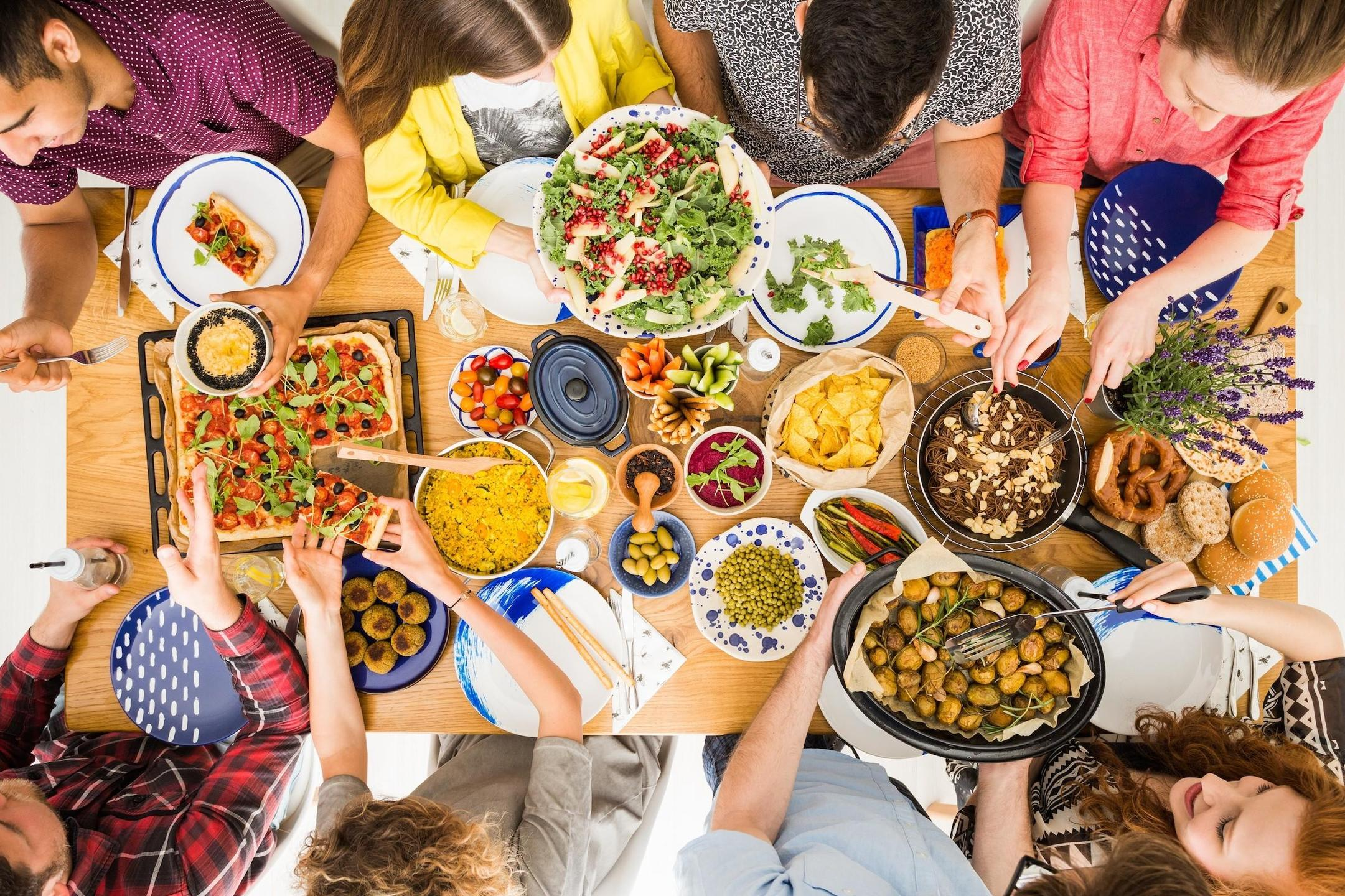 friends enjoying a vegan family meal at a table full of plant-based recipes