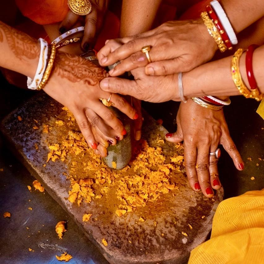 Cooking Vegan Indian Recipes with many hands grinding Indian spices