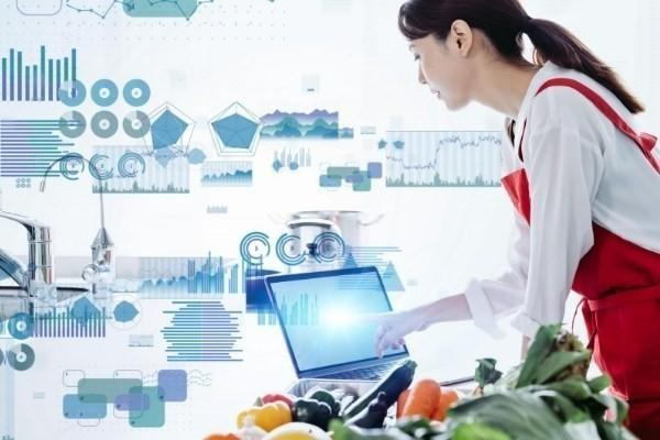 vegan science with vegetables, woman in an apron with a  computer