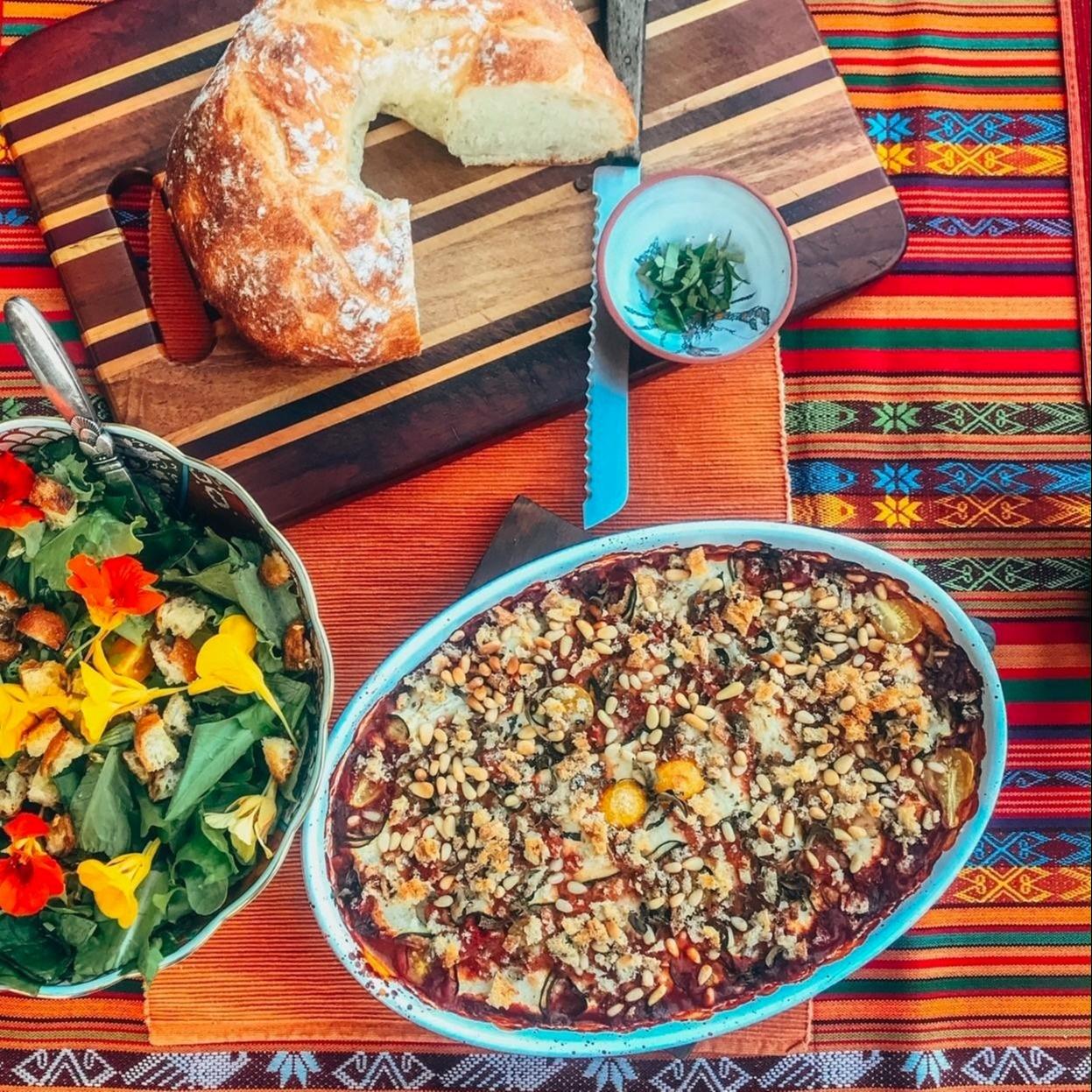 birds eye view of salad, bread and vegan involtini
