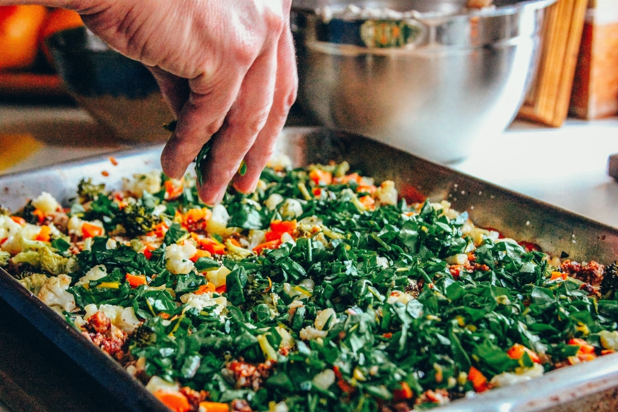 sprinkling greens on a pan of Your Vegan Family lasagne