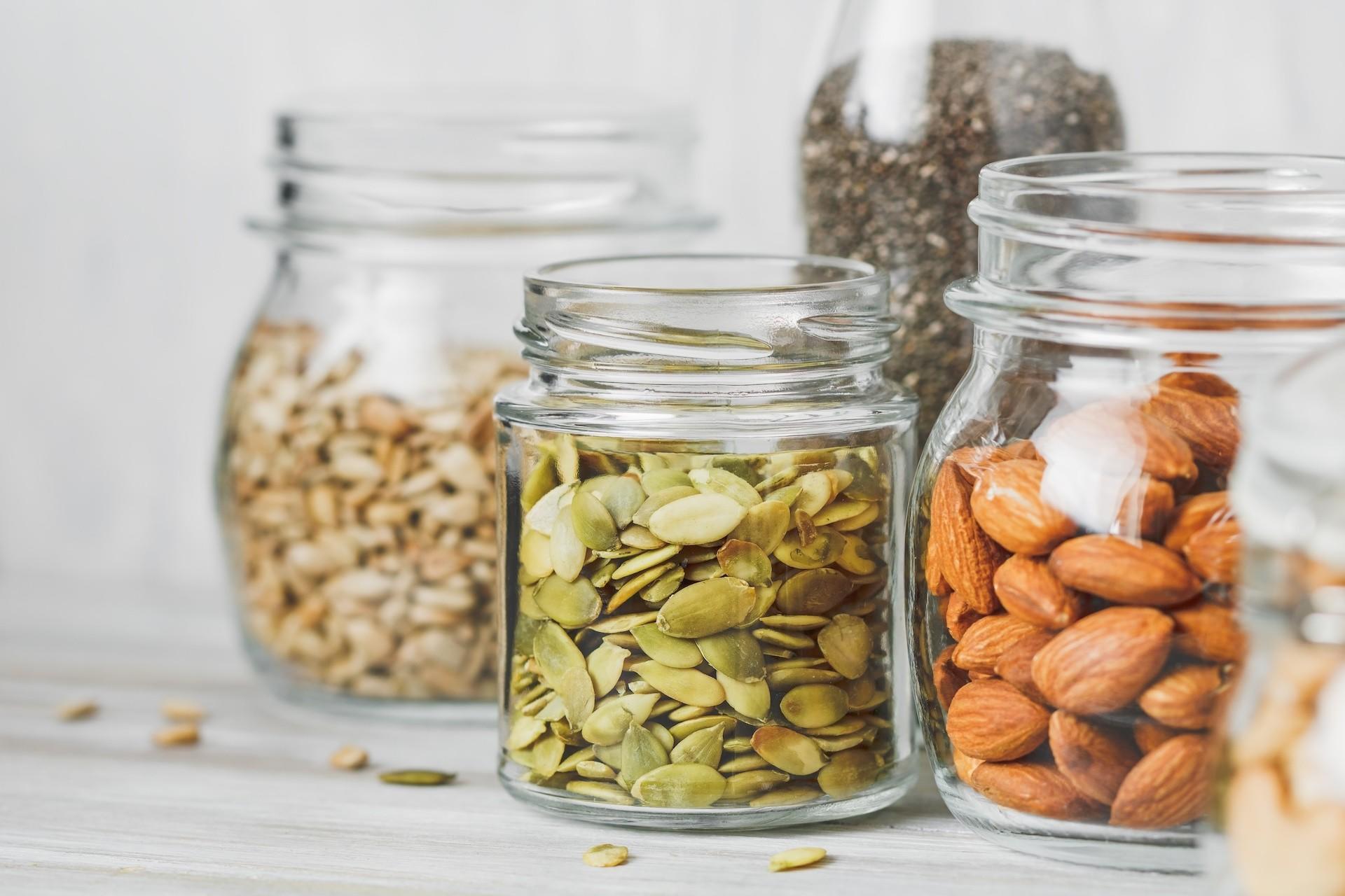 Clear glass jars of vegan snacks: almonds, pumpkin seeds, sunflower seeds