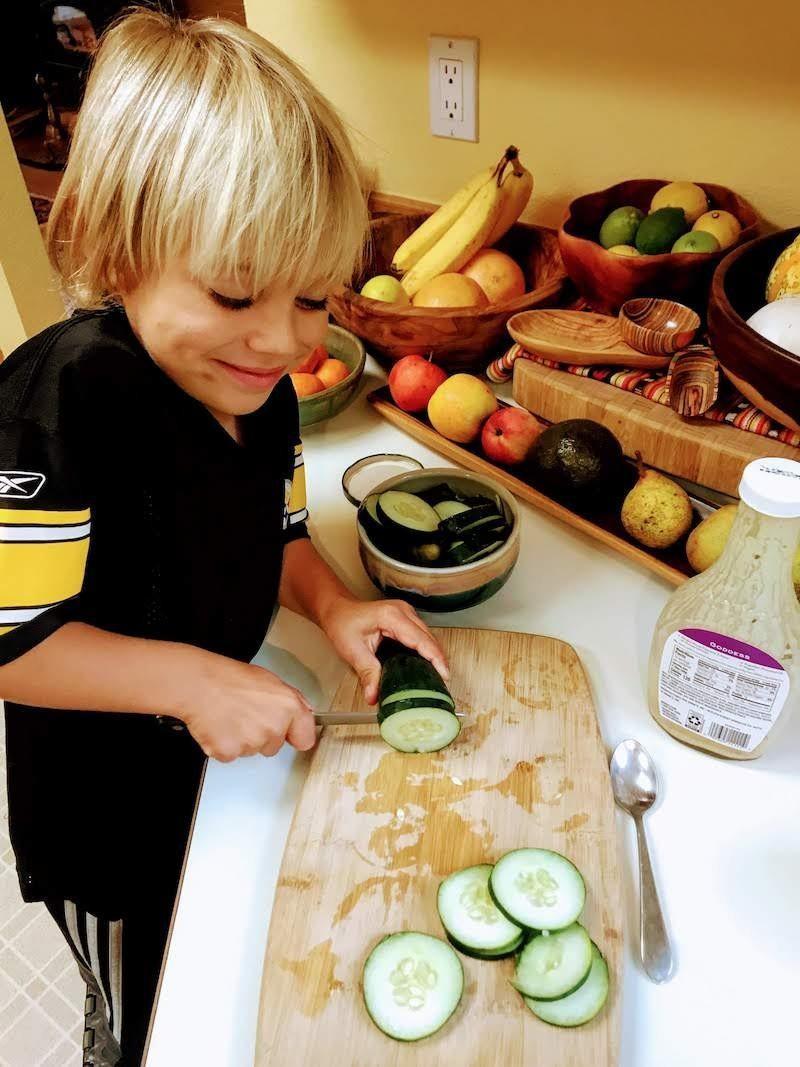 vegan kid cutting cucumbers next to bowls of fruit