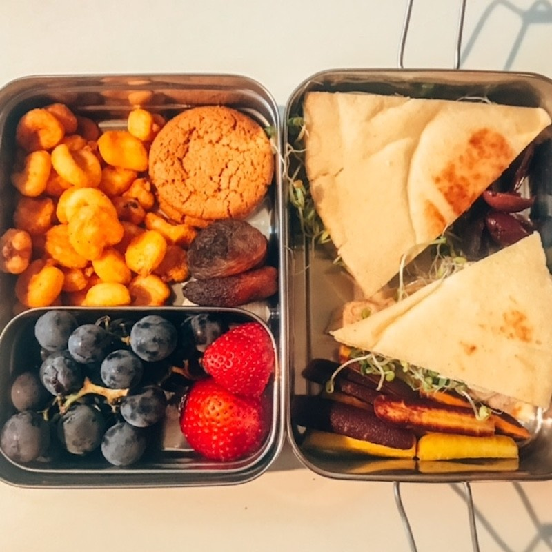 Your Vegan Family Vegan kids lunch: hummus, pickles, and sprouts pita sandwich, baby carrots, grapes, strawberries, dried nectarines, Inca corn snack, ginger cookie.