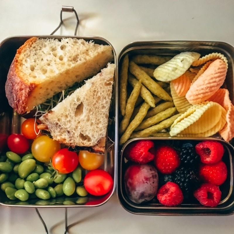 Vegan kids lunch cheese, tofurkey, and sprouts sandwich with bursting tomatoes, edamame, blackberries, raspberries, a plum, vegetable crisps, snap pea crisps