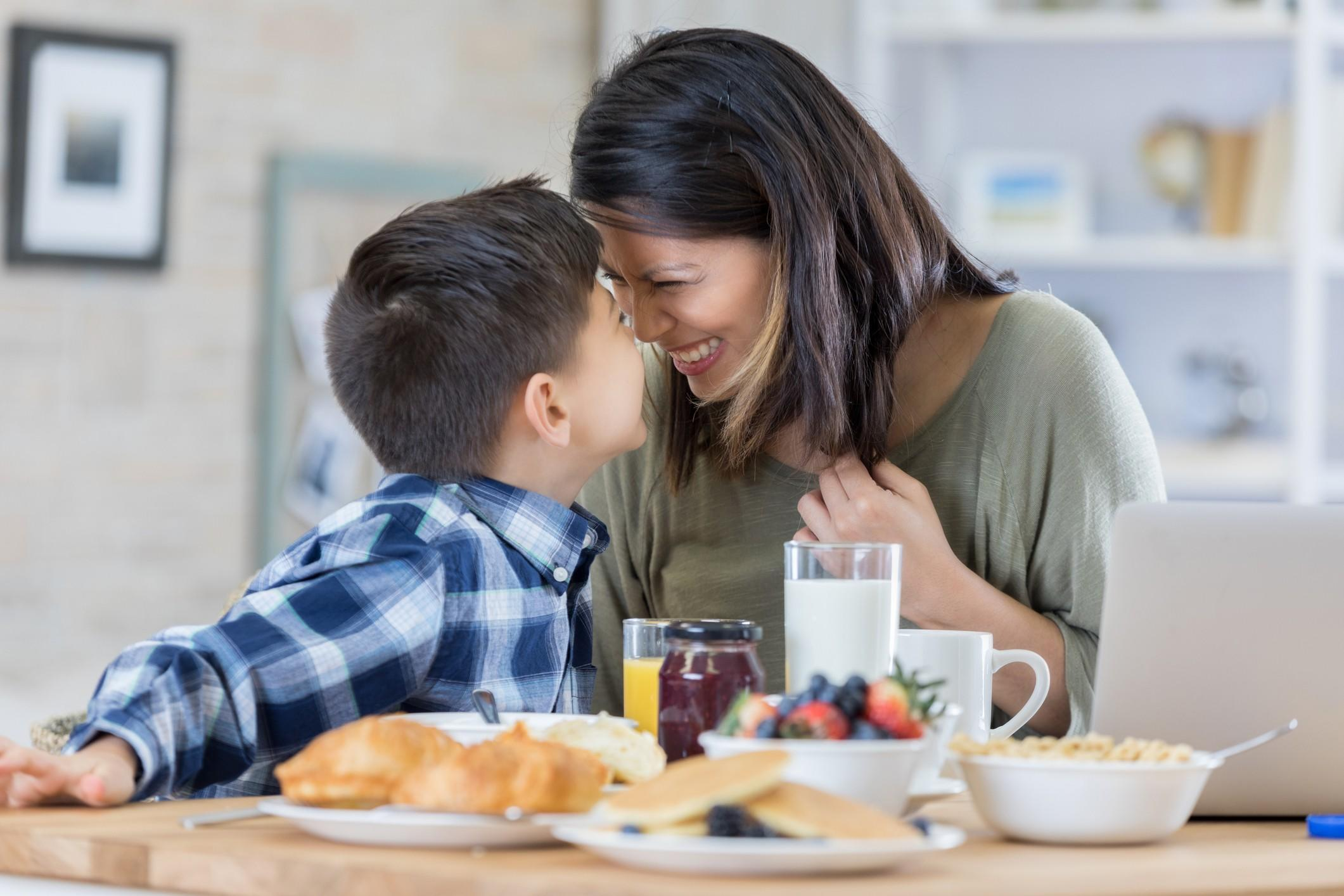 Child being fed by mother and affectionate moment