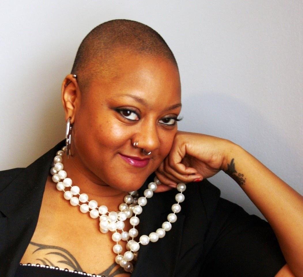 Headshot of Marla Steward, bald, black woman wearing a large pearl necklace