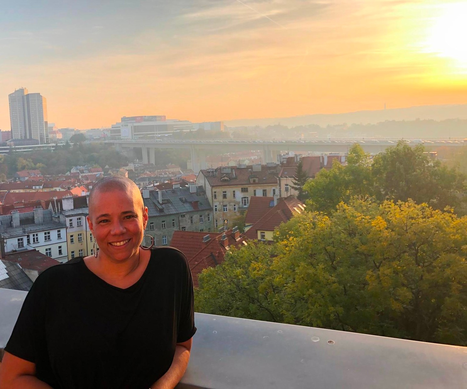 Arika in Prague standing in front of a sunset above the city.