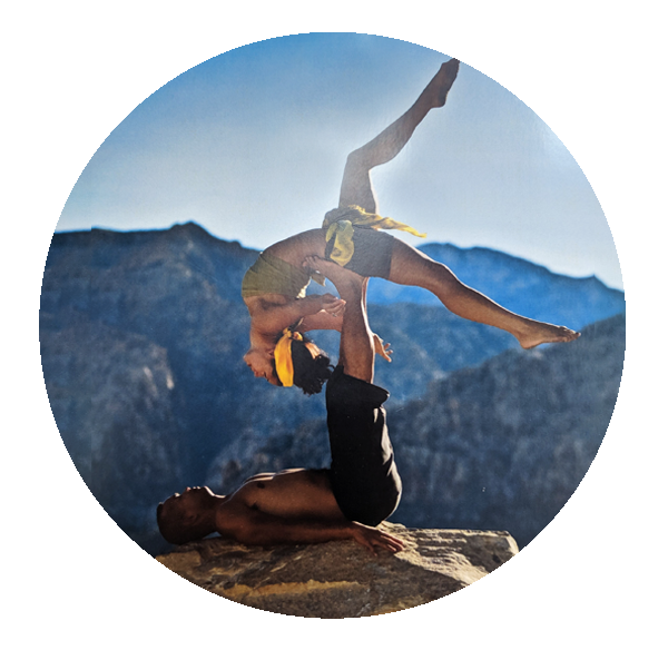 Alvin and Jada Tam in AcroYoga back band pose on a cliff overlooking the mountains
