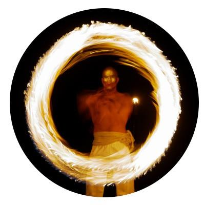 Alvin is spinning fire in the dark with glowing circle of light in front of him