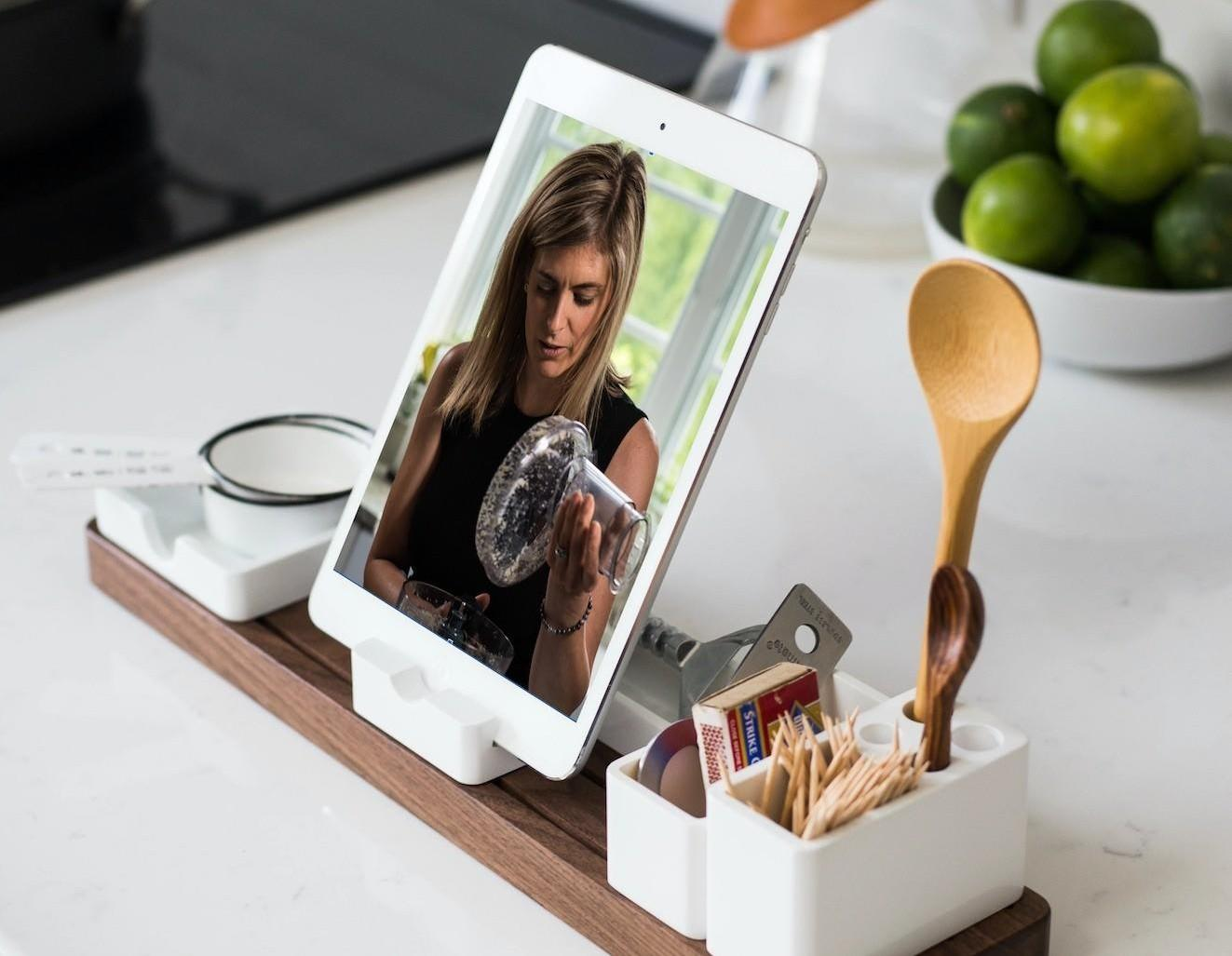 Ipad on stand in kitchen with image of Megan and a food processor on it