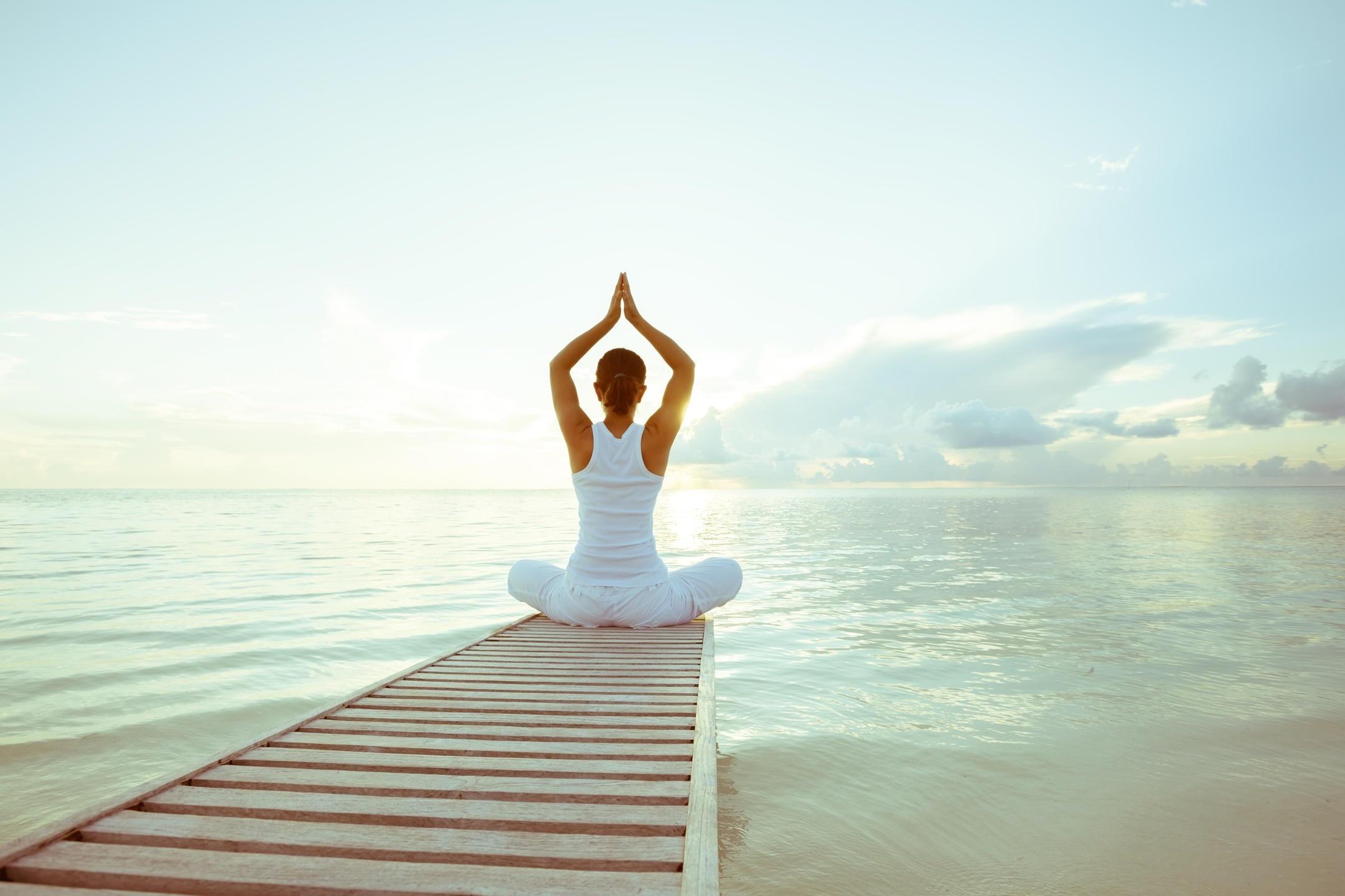 Frau beim Yoga am See