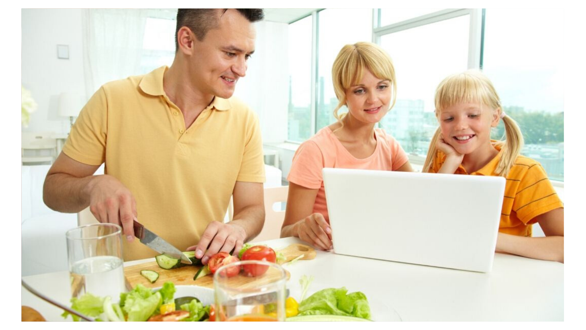 family preparing healthy meal while looking online