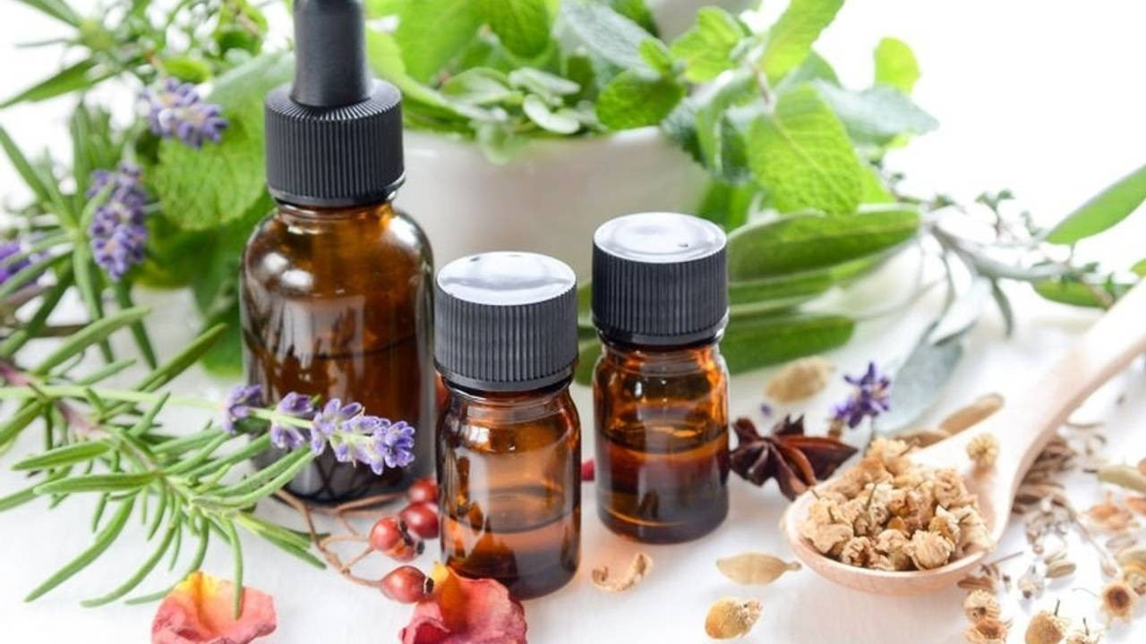 Essential oils surrounded by herbs, flowers and resins