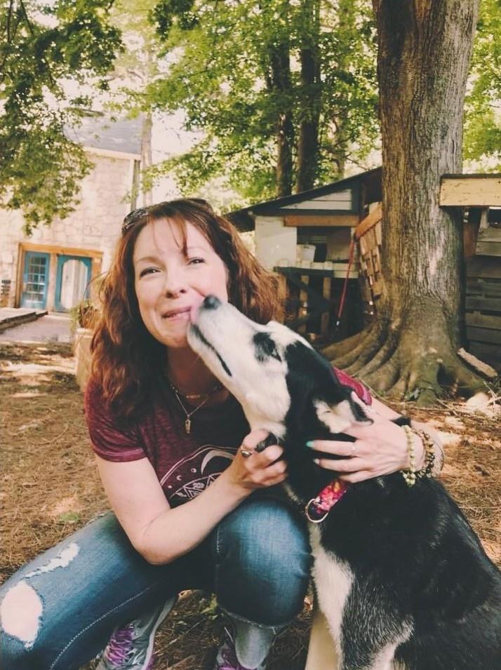 woman crouching next to black and white dog