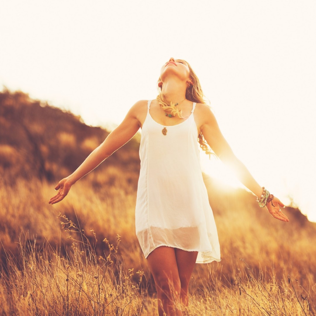 woman in white dress in field with sunset