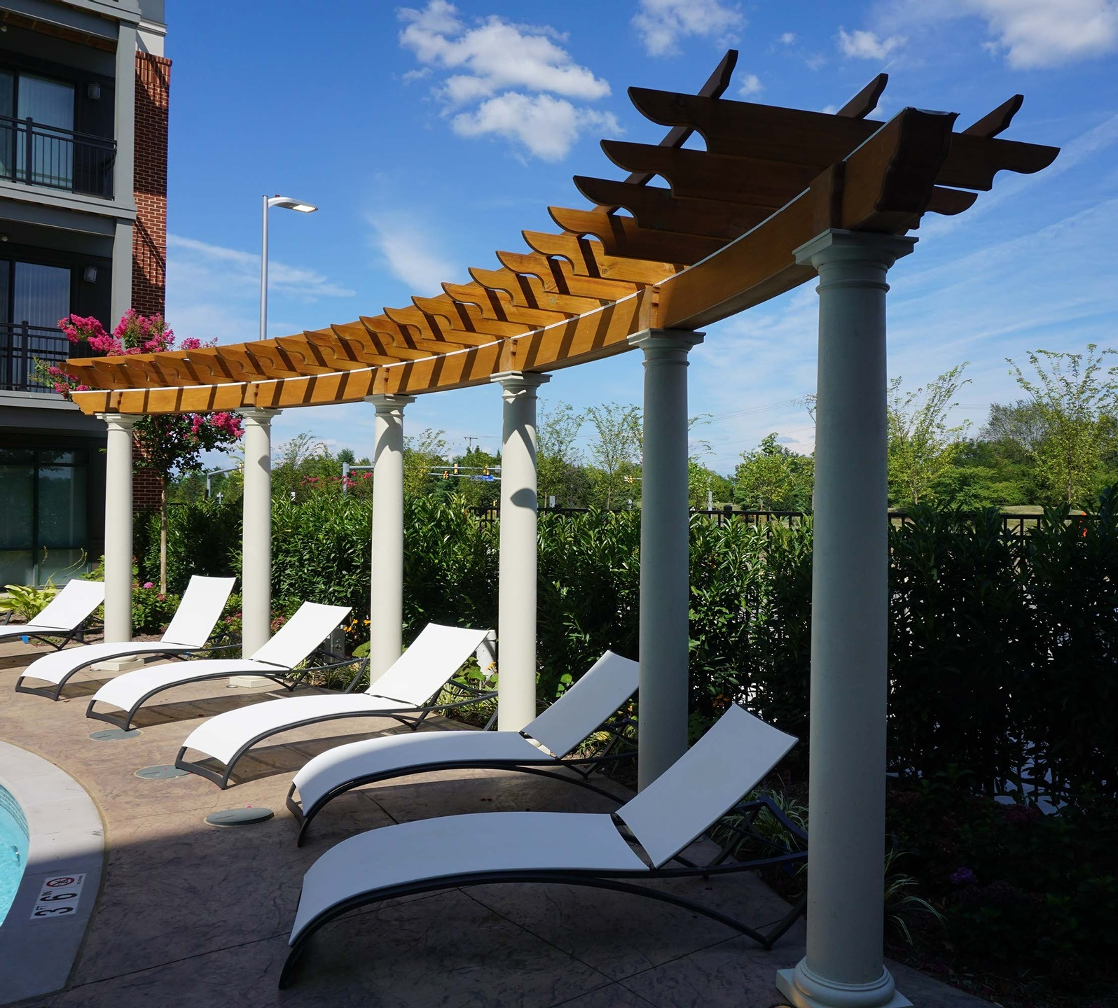 Curved pergola colonnade with round Tuscan columns and cedar wood elements
