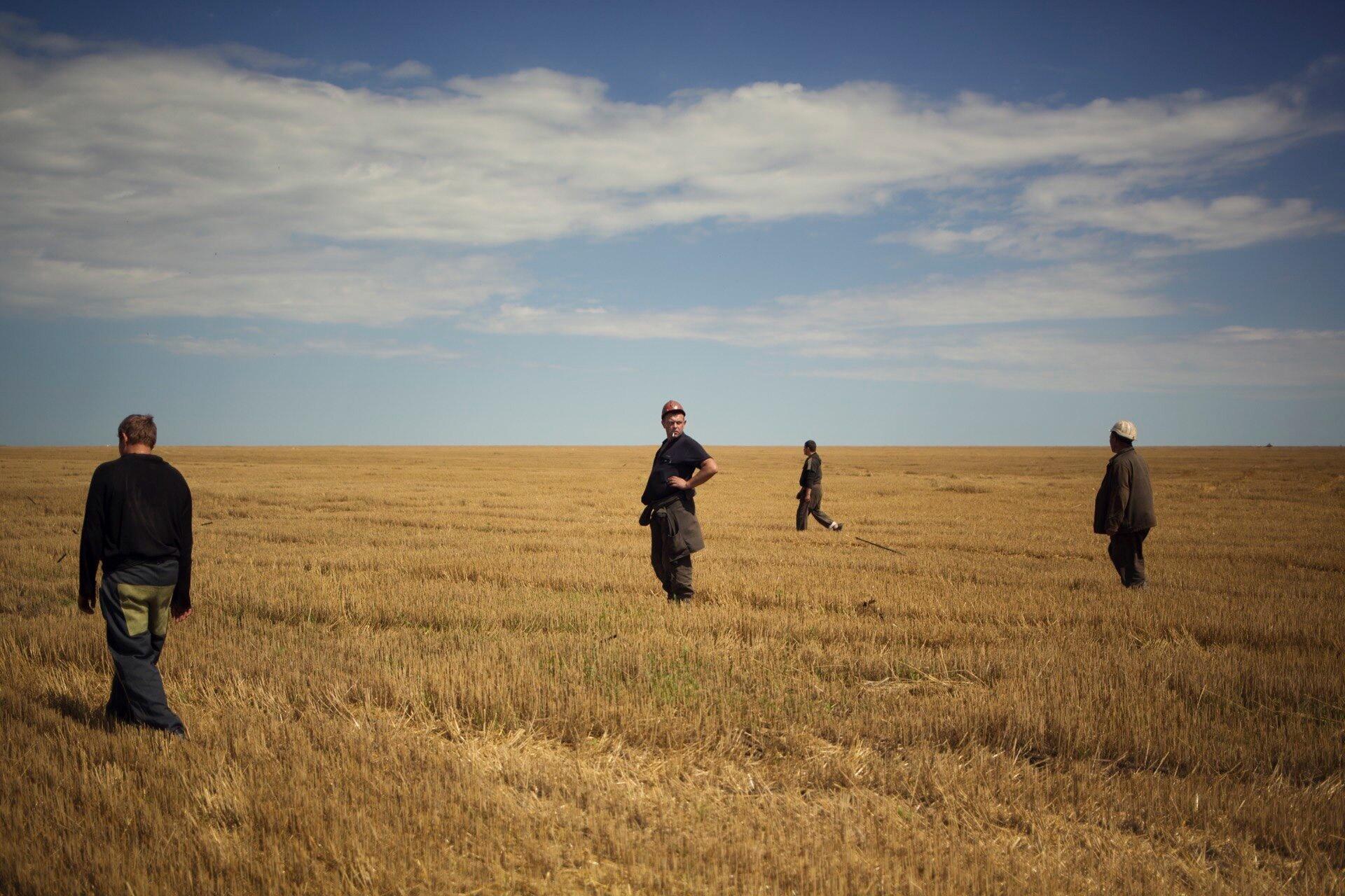 Fotografi av menn i en åker. Foto av Kyrre Lien
