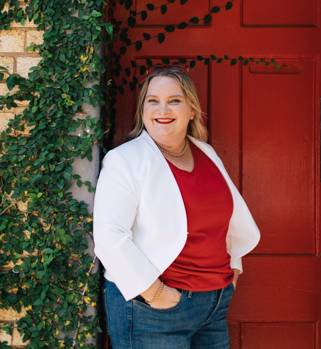 Power woman wearing a red shirt and white blazer standing against red door with ivy growing over it- Juanita Wheeler from Full and Frank for the cover of Viva La Flora Live Podcast