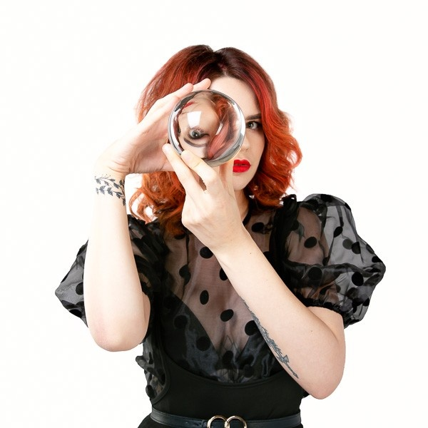 A photograph of a woman looking through a crystal ball with her eye refracted