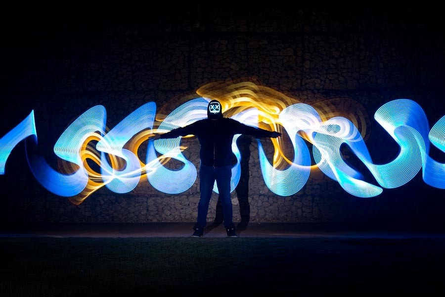 A light painted photo of a man wearing a mask at night