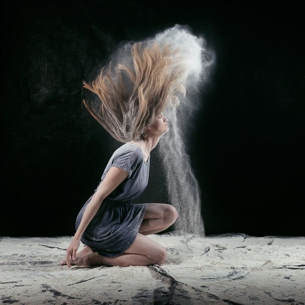 A photograph of a woman flicking flour from her hair