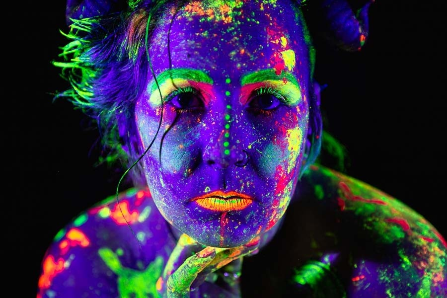 A photograph of a face painted under black light UV
