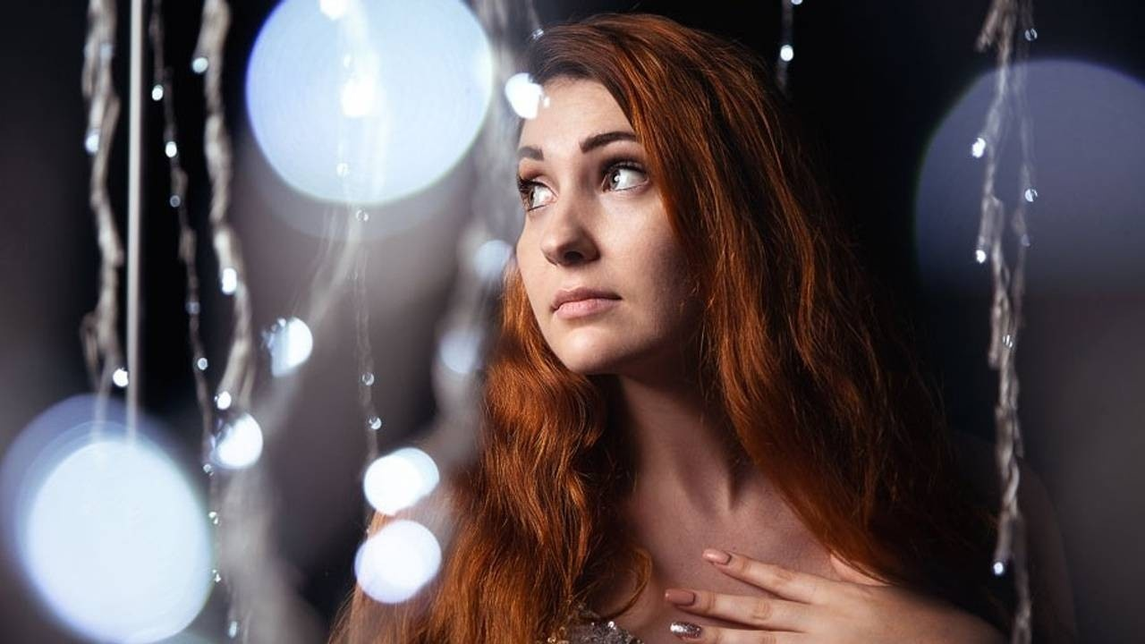 A photograph of a red haired woman surrounded by strings of christmas lights and bokeh