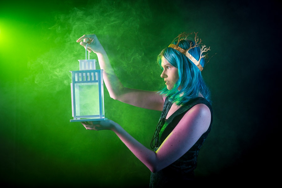 A photograph of an elven woman wearing a crown and holding a lantern surrounded by green smoke