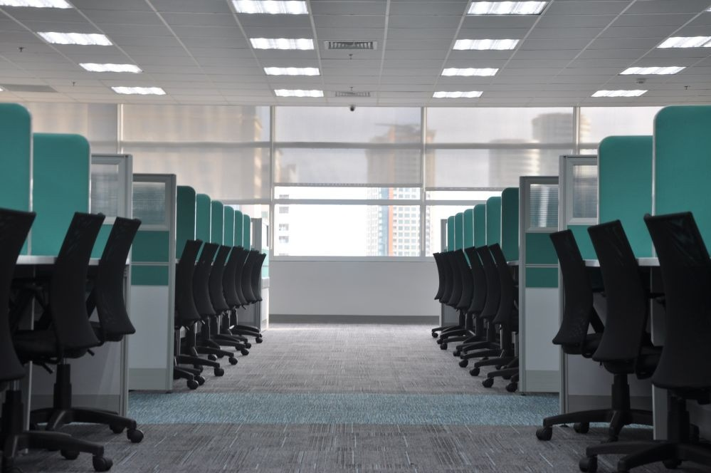 green cubicles with row of black office chairs