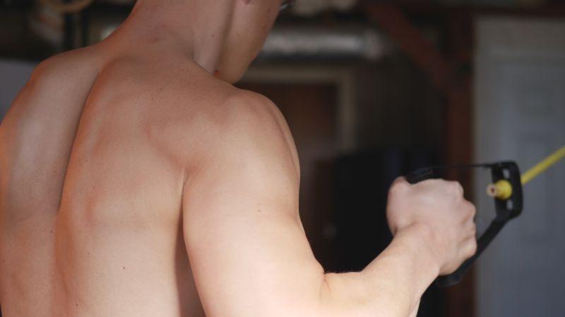 man pulling band doing back exercise