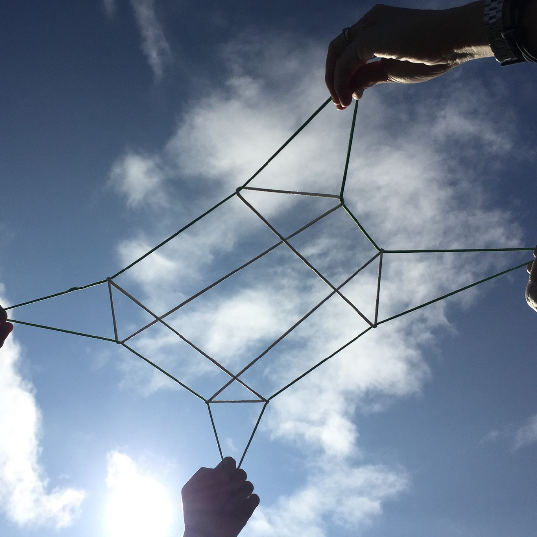 Two sets of hands holding a string figure (hei) up to the sky.