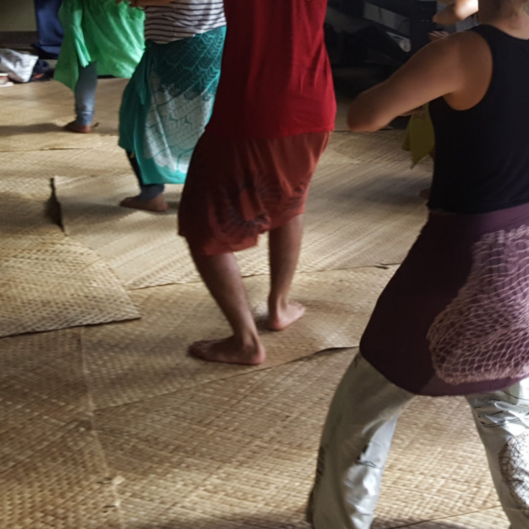 People dancing hula on mats of woven pandanus leaves (lauhala).