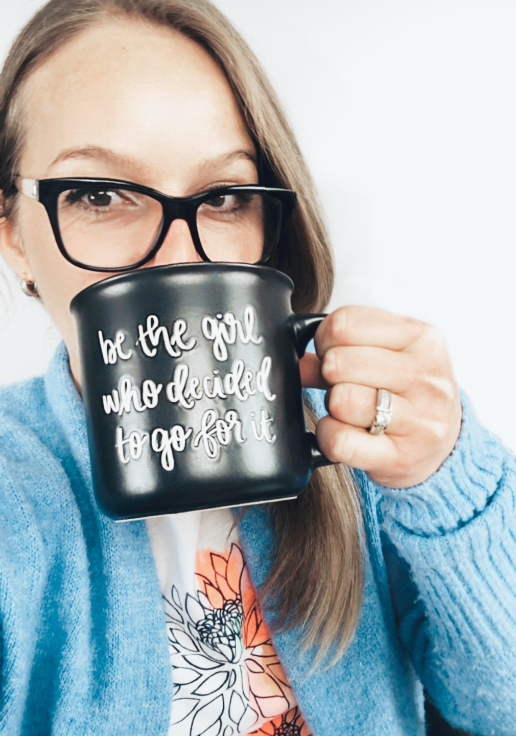 Katarina Hadden with a cup of coffee. Cup has a quote