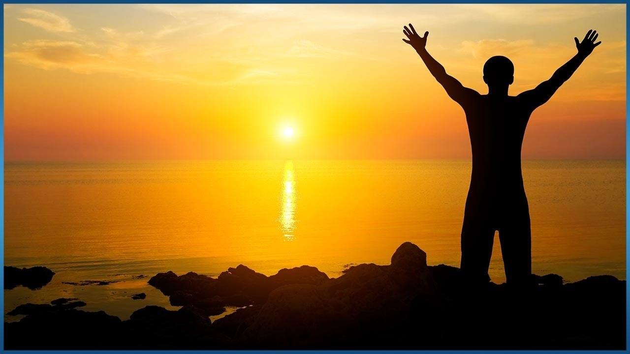 silhouette of man standing in front of sunset with arms raised