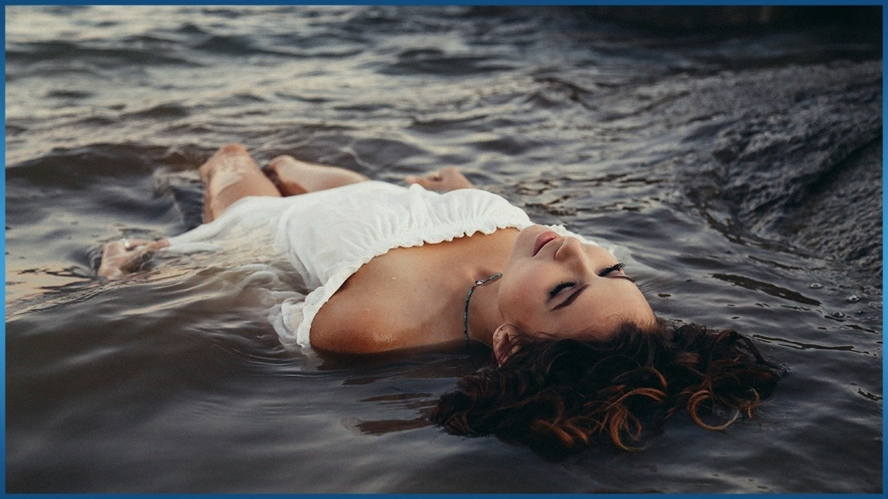 woman in white dress laying in ocean