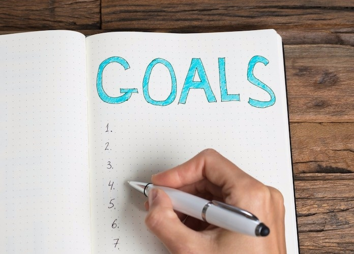woman writing goals in notebook