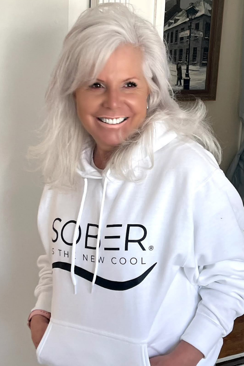 Woman with white hair and white sweatshirt smiling. Sober is the New Cool, Kim Bellas