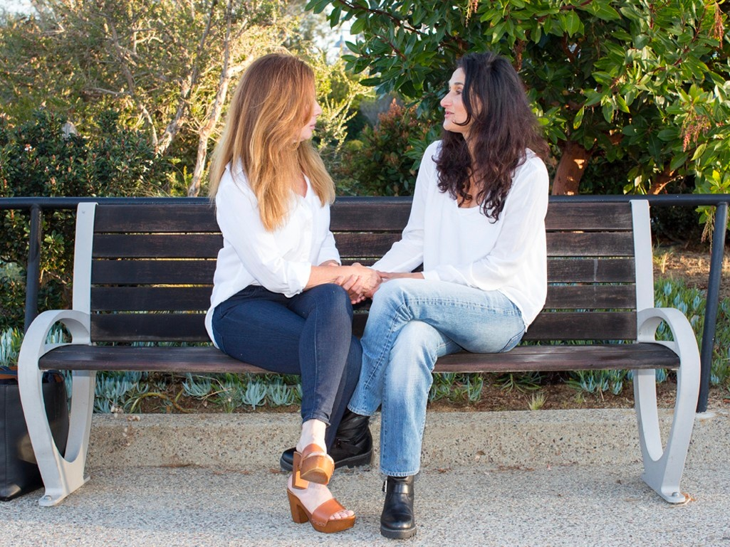 Two ladies on a park bench talking and comforting