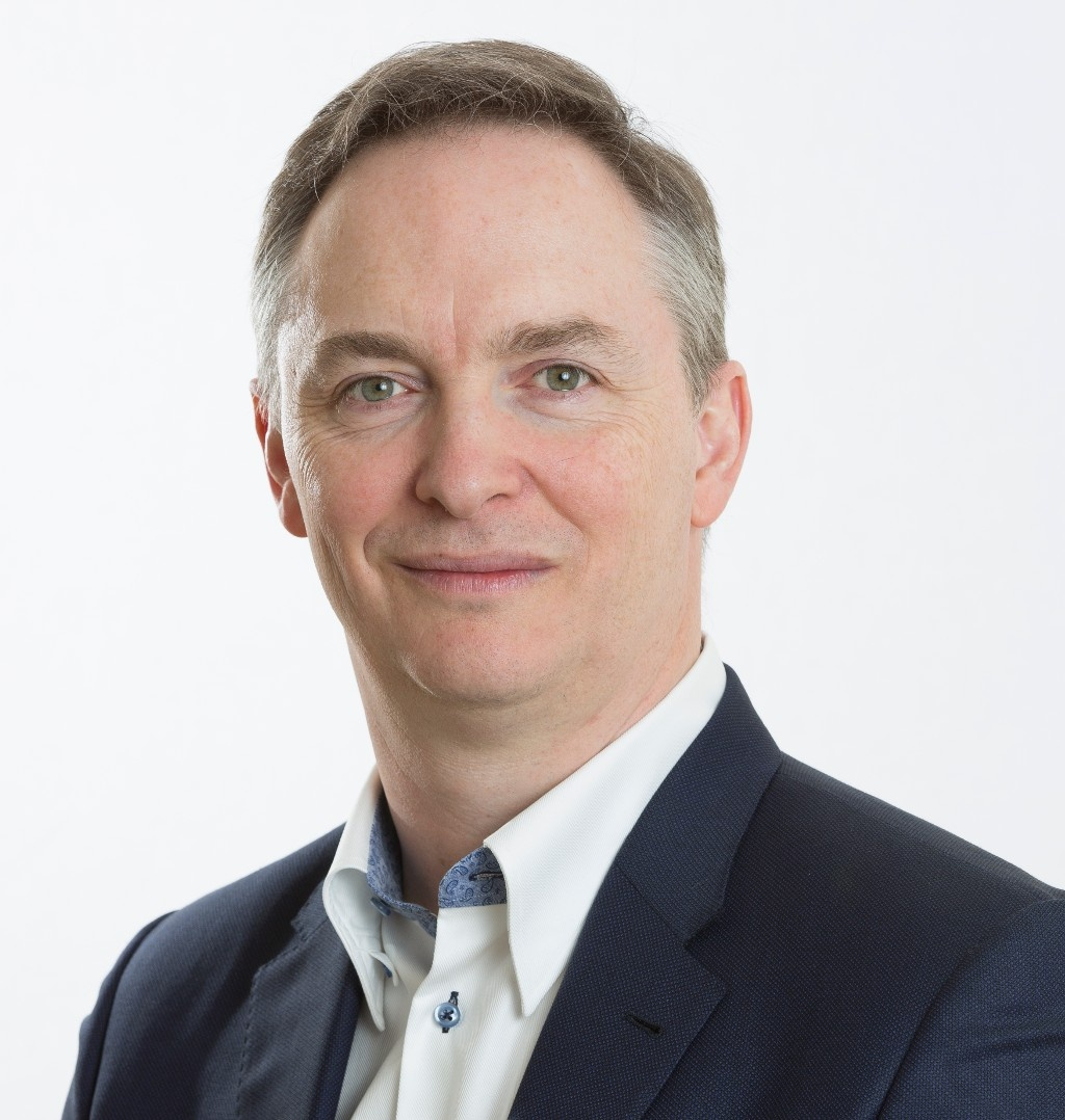 A head and shoulders photo of a man, Stuart Morris, in a suit.