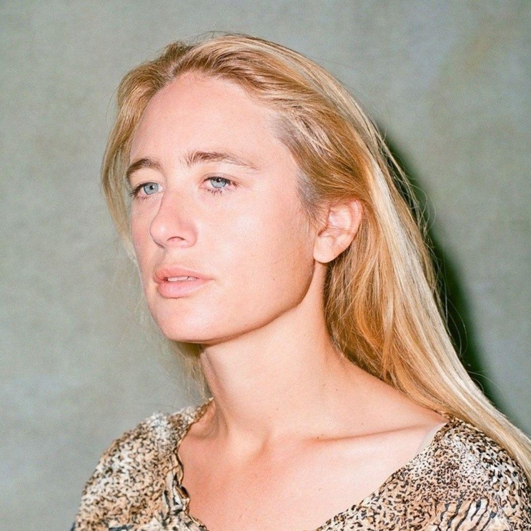 Headshot of Maya F. Blond white woman looking wistfully away from camera.