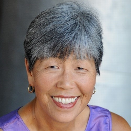 Photo of Gail Whang, Korean woman with salt and pepper pixie cut and a big smile