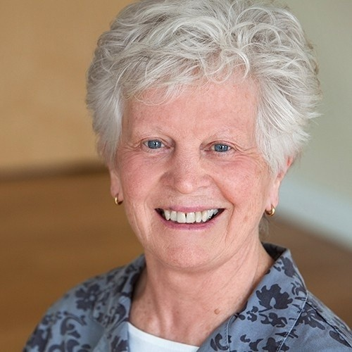 Photo of Maureen Berndt white woman with short curly white hair and soft blue eyes