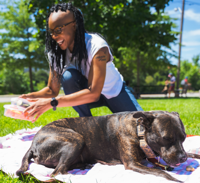 Black woman sits on a park bench with a medium size pitbull mix who are both smiling towards the camera.