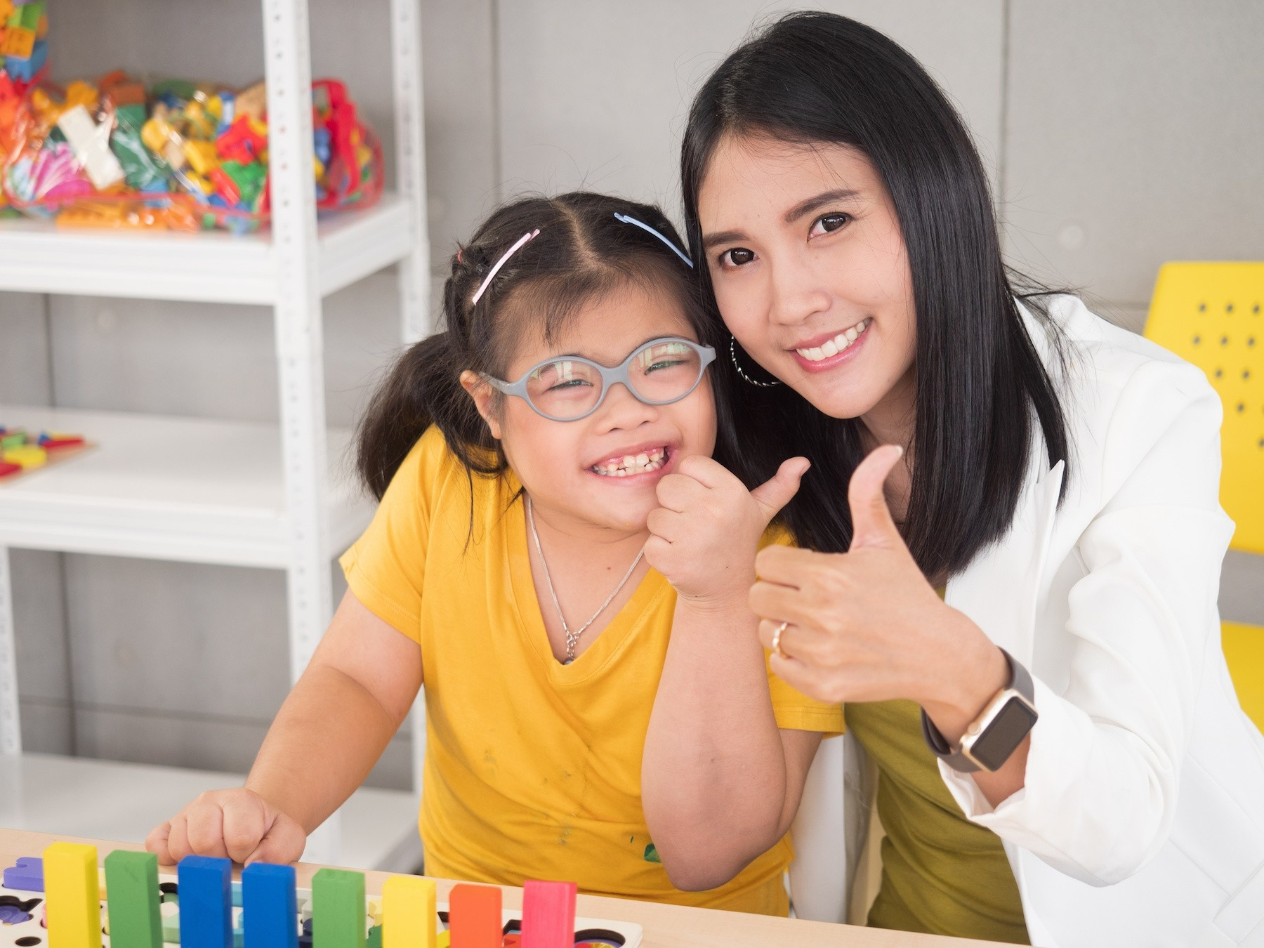 Teacher and student smiling and giving thumbs up