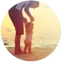 Silhouette of a parent and toddler walking the beach