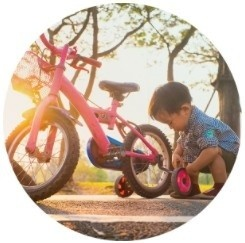 Child putting training wheels on a bike
