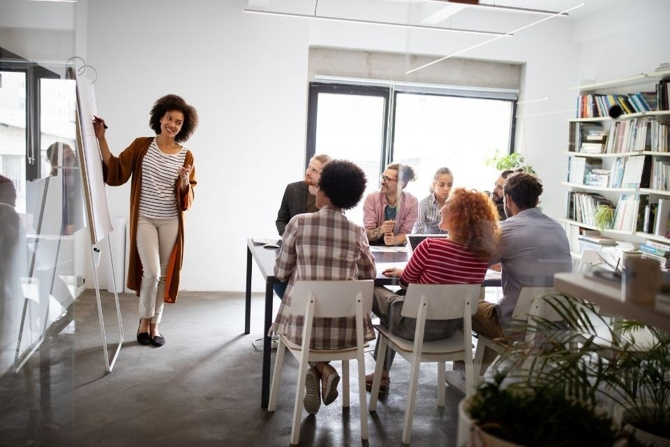 Black woman standing at a whiteboard presenting to a group of people sitting around a table.